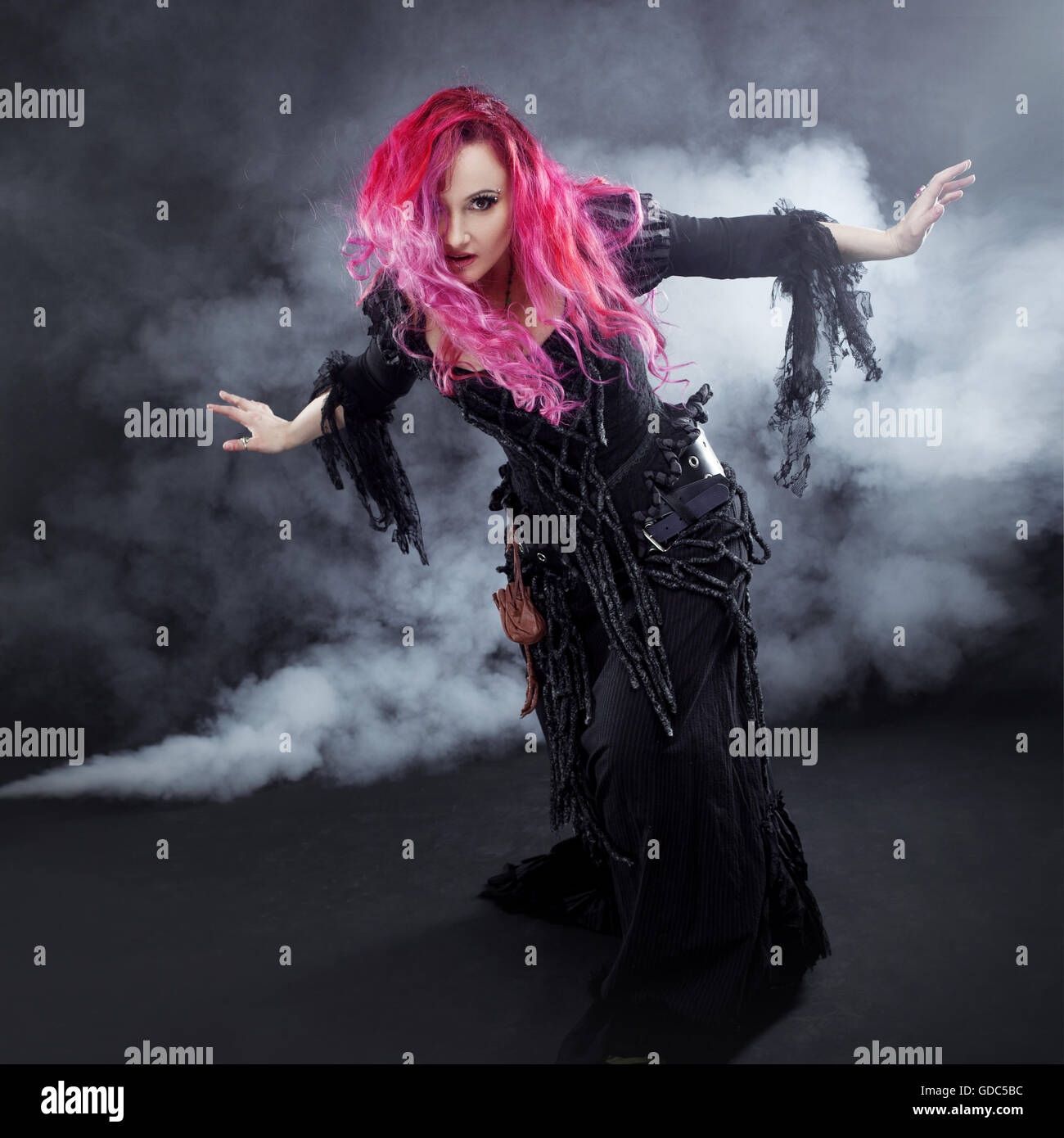 Halloween Witch creates magic. Attractive woman with red hair in witches costume - Stock Image