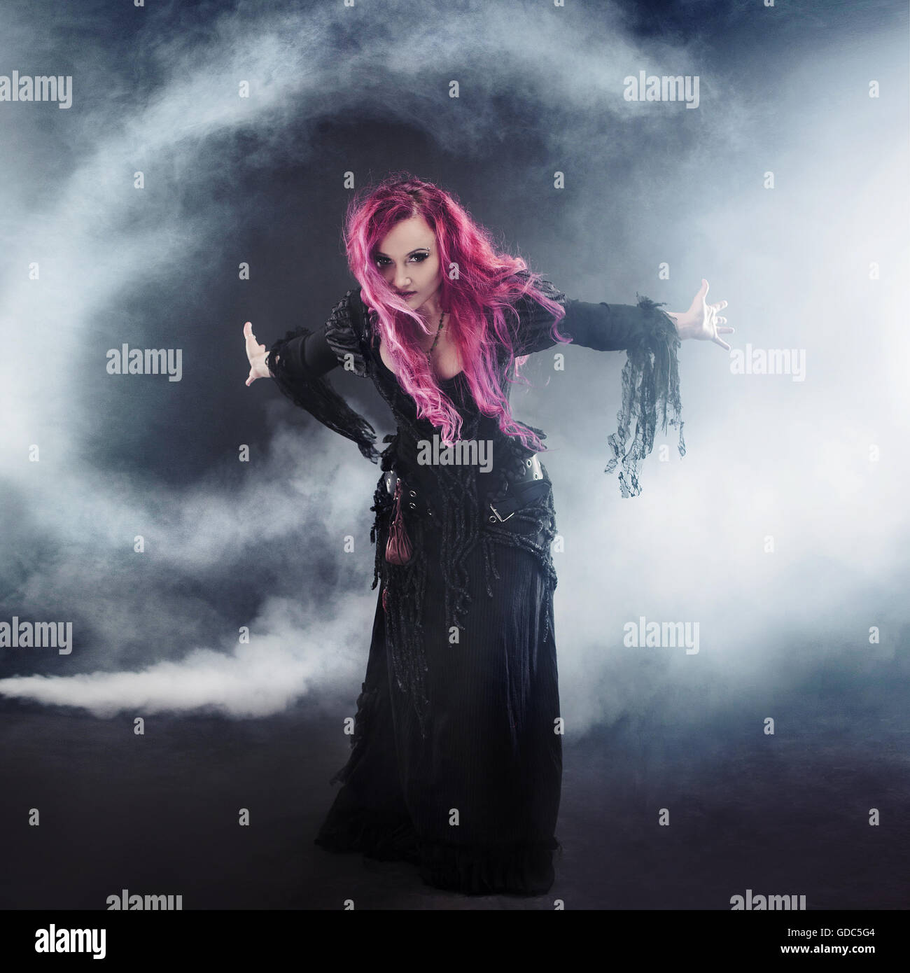 Halloween Witch creates tornado. Attractive woman with red hair in witches costume standing outstretched arms, strong - Stock Image