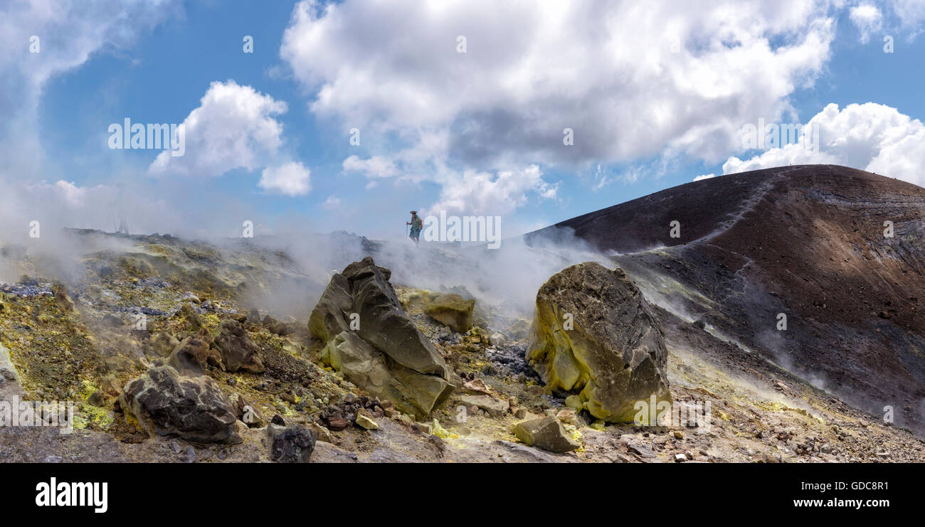 Hikers in the fumes of an active volcano - Stock Image