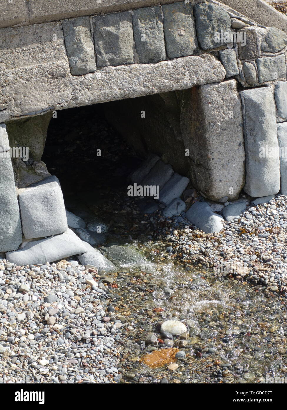 An old drain channel or irrigation pipe on a beach - Stock Image