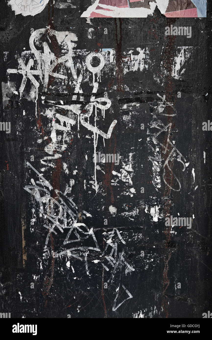 Graffiti on a rough textured city wall background - Stock Image
