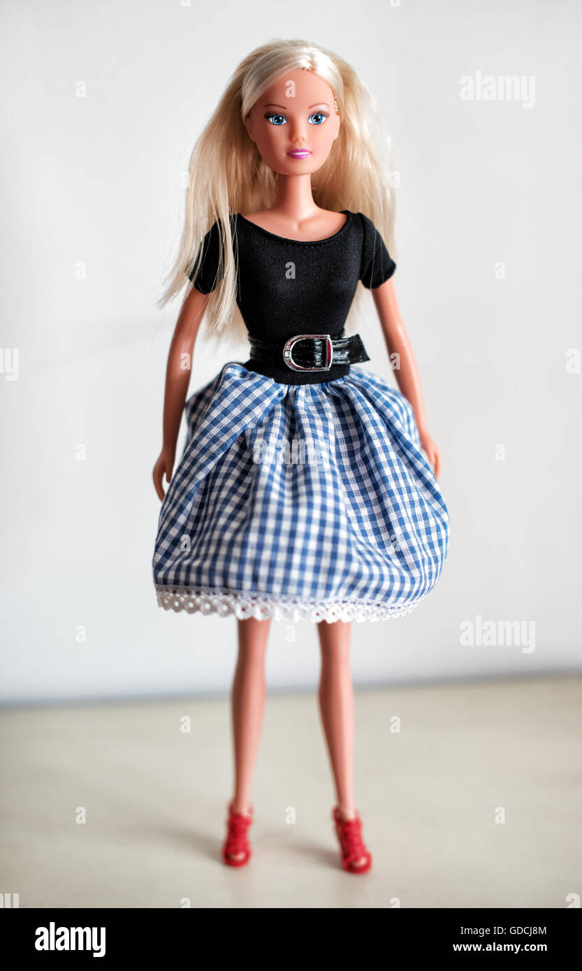 Single blond toy doll in knee length checkered blue and white skirt, black blouse and red shoes - Stock Image