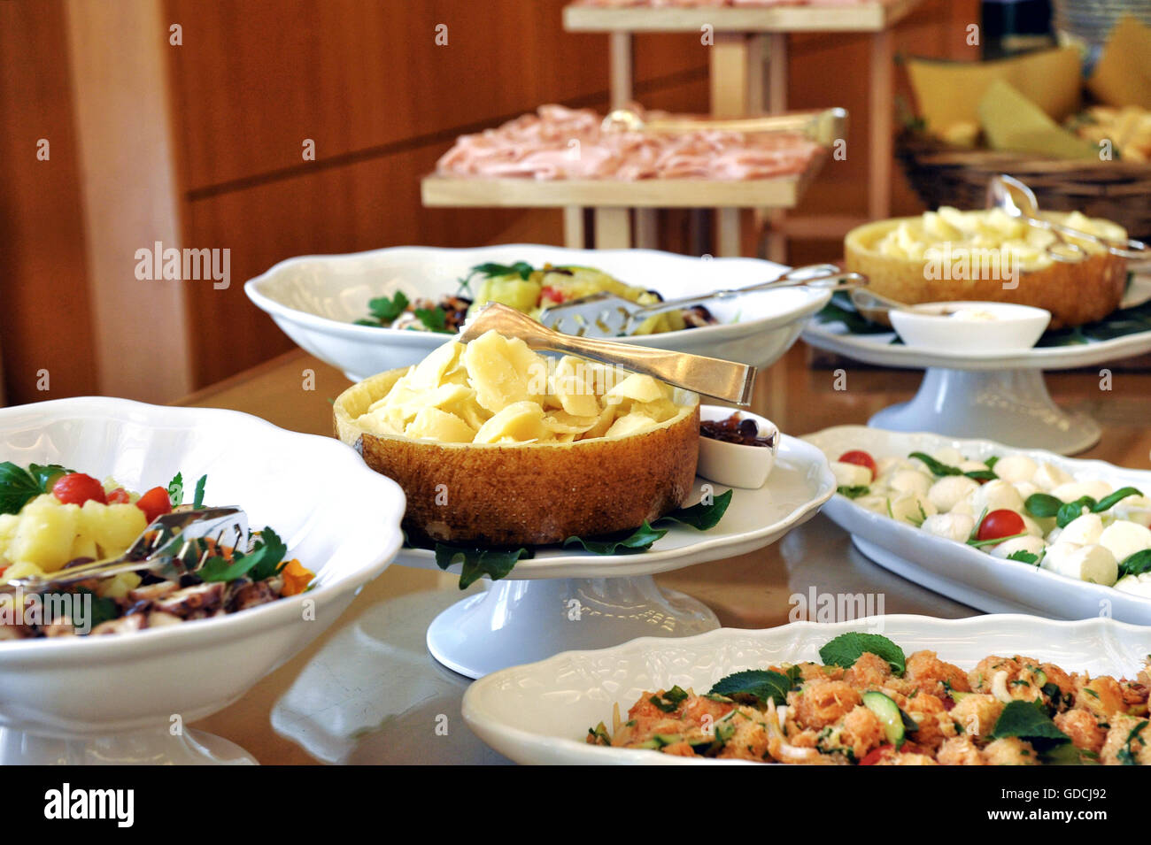 Selection of sliced cold meat, fish and side dishes on a buffet table at a catered event viewed close up - Stock Image