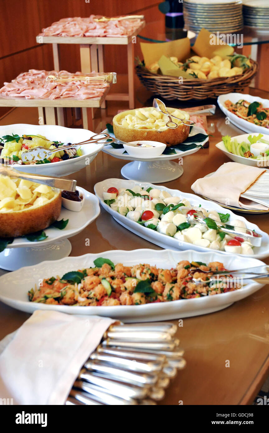Assortment of food on a cold buffet at a hotel or catered event with sliced cold meats, salads and fish on display - Stock Image