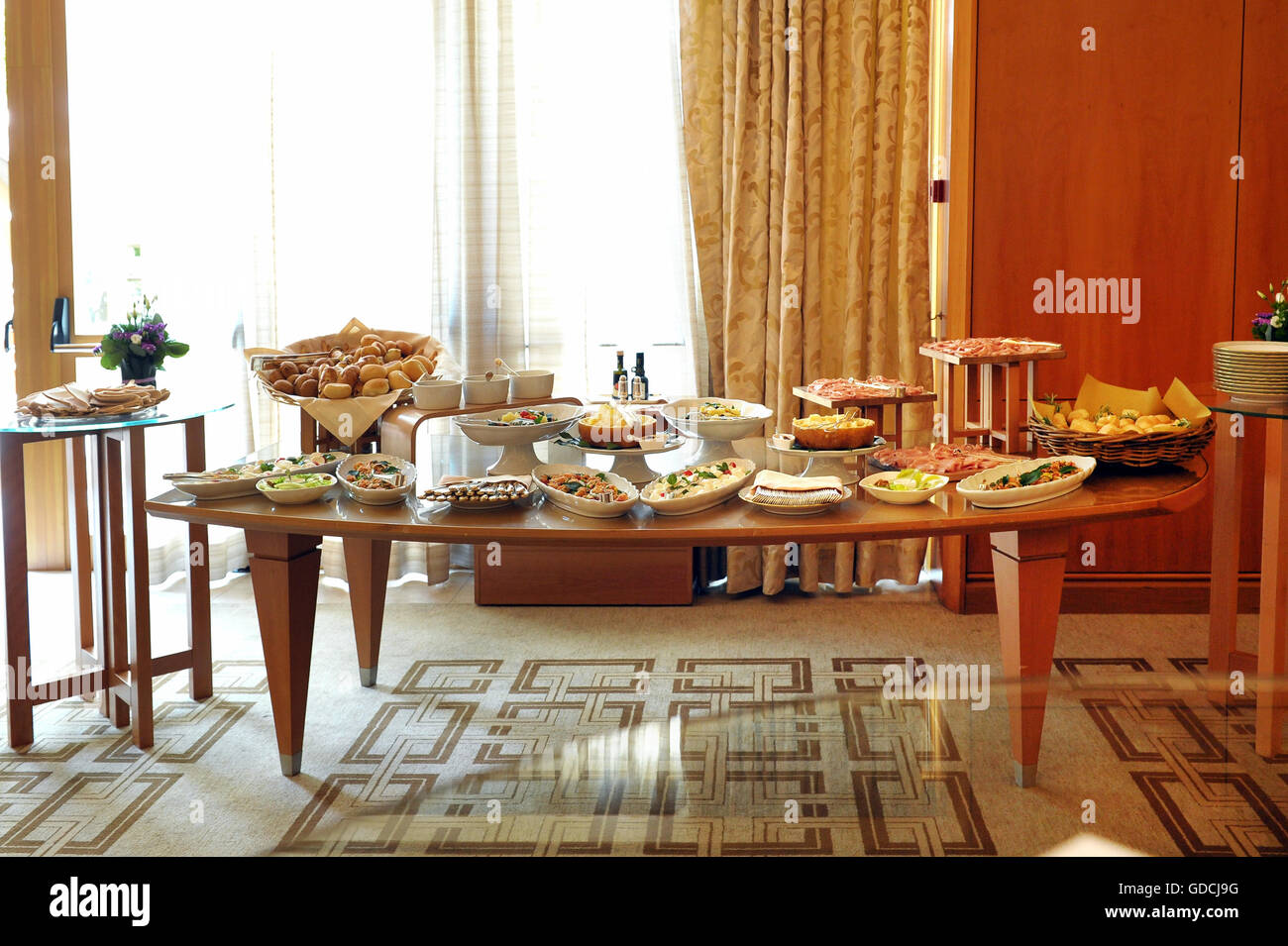 Buffet table laden with a selection of food in a restaurant or hotel with cold mets, fish and salads in front of - Stock Image