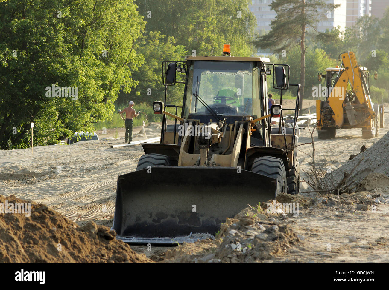 bulldozer, forklift and workers at the construction road junction in Moscow - Stock Image
