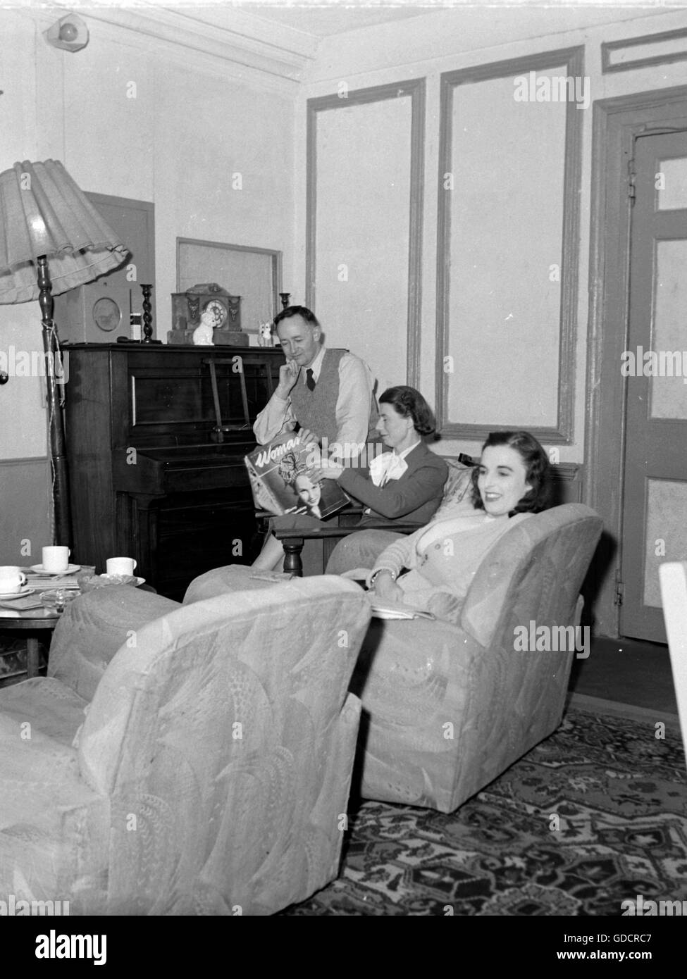 A typically furnished family living room c1950. Mother is reading 'Woman Magazine'. Photograph by Tony Henshaw - Stock Image
