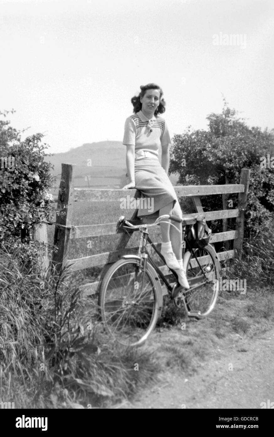A young woman poses on a gate with her bicycle c1935. A lovely pose dressed in stylish knitted fashion with nice - Stock Image
