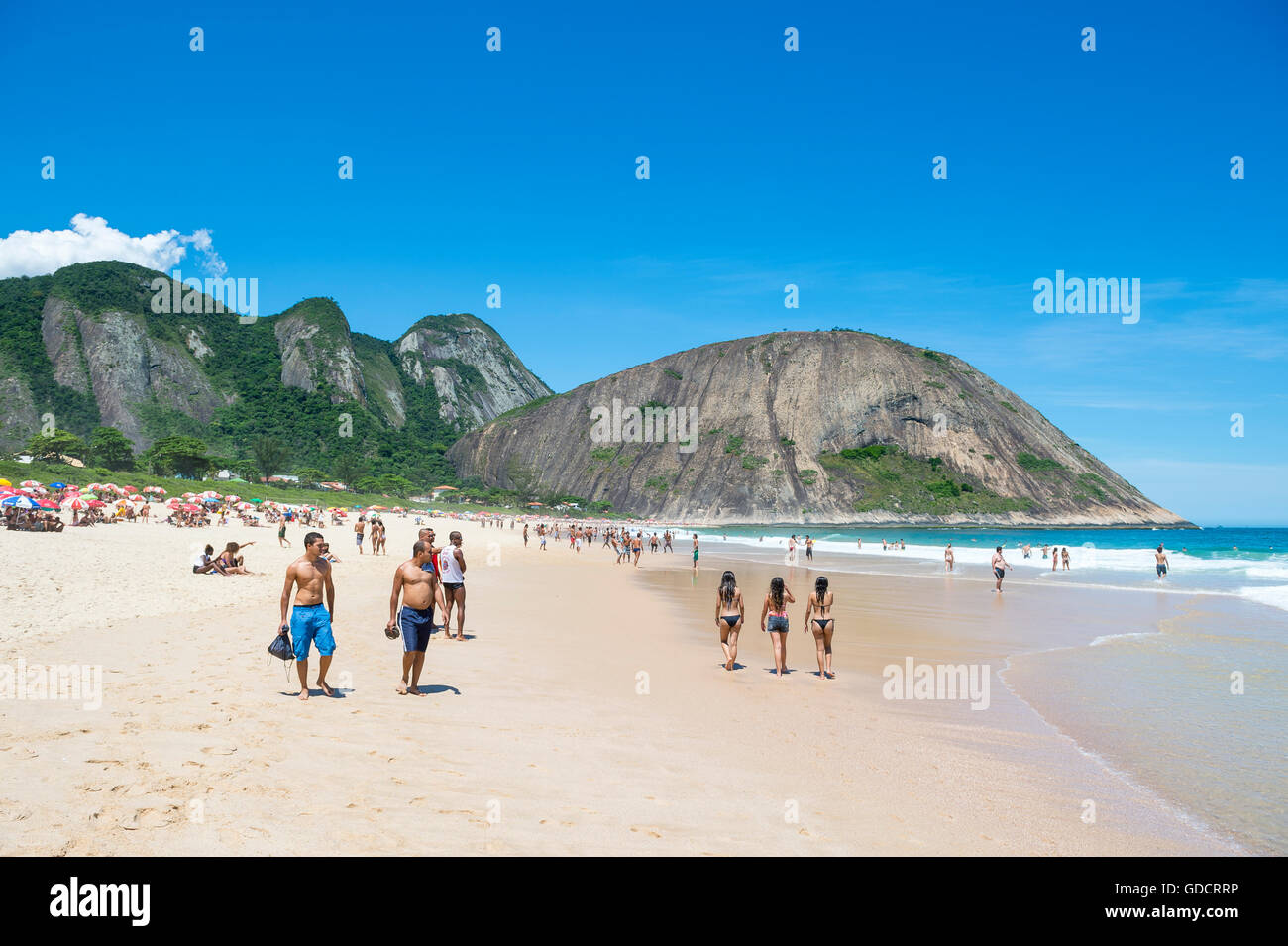 RIO DE JANEIRO - OCTOBER 31, 2015: Young Brazilians walk on the shore of Itacoatiara Beach, popular for surfing - Stock Image