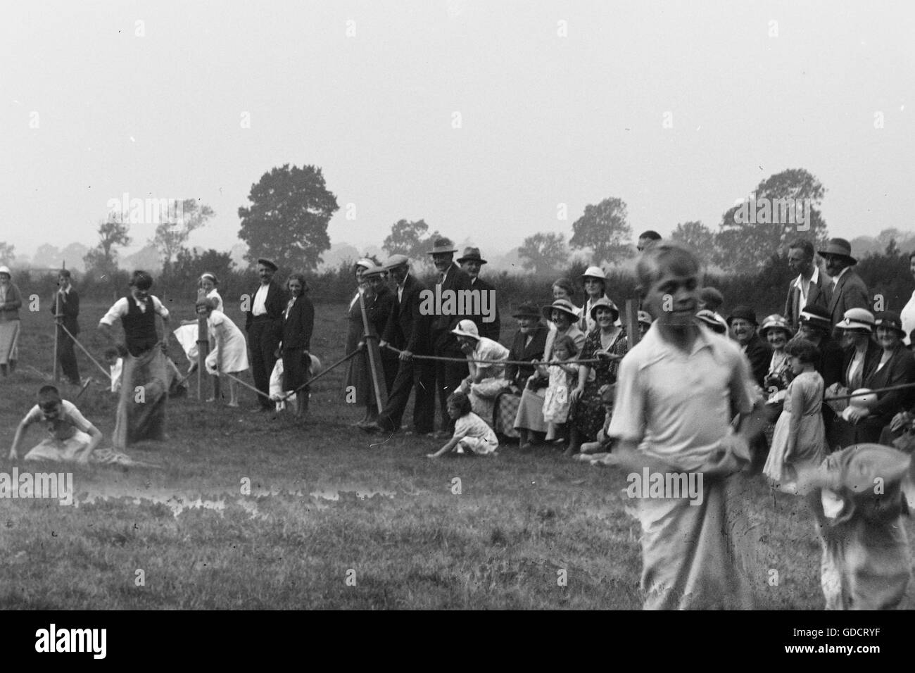 Boys in a sack race. Both boys and crowd are clearly enjoying the race. Unknown venue c1930. Photograph by Tony - Stock Image