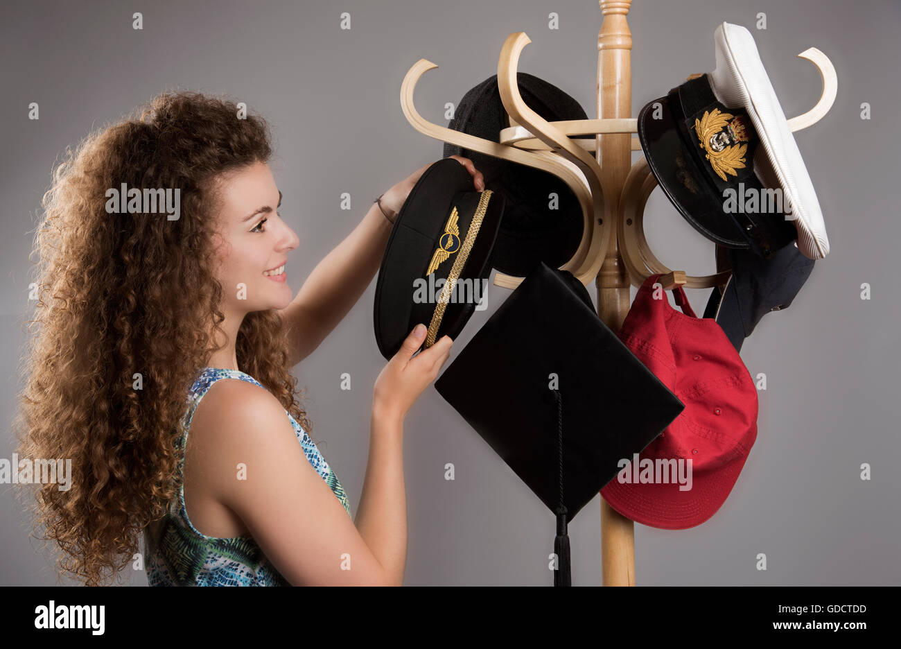 Young woman arranging hats from a selection of professions on a hat stand - Stock Image