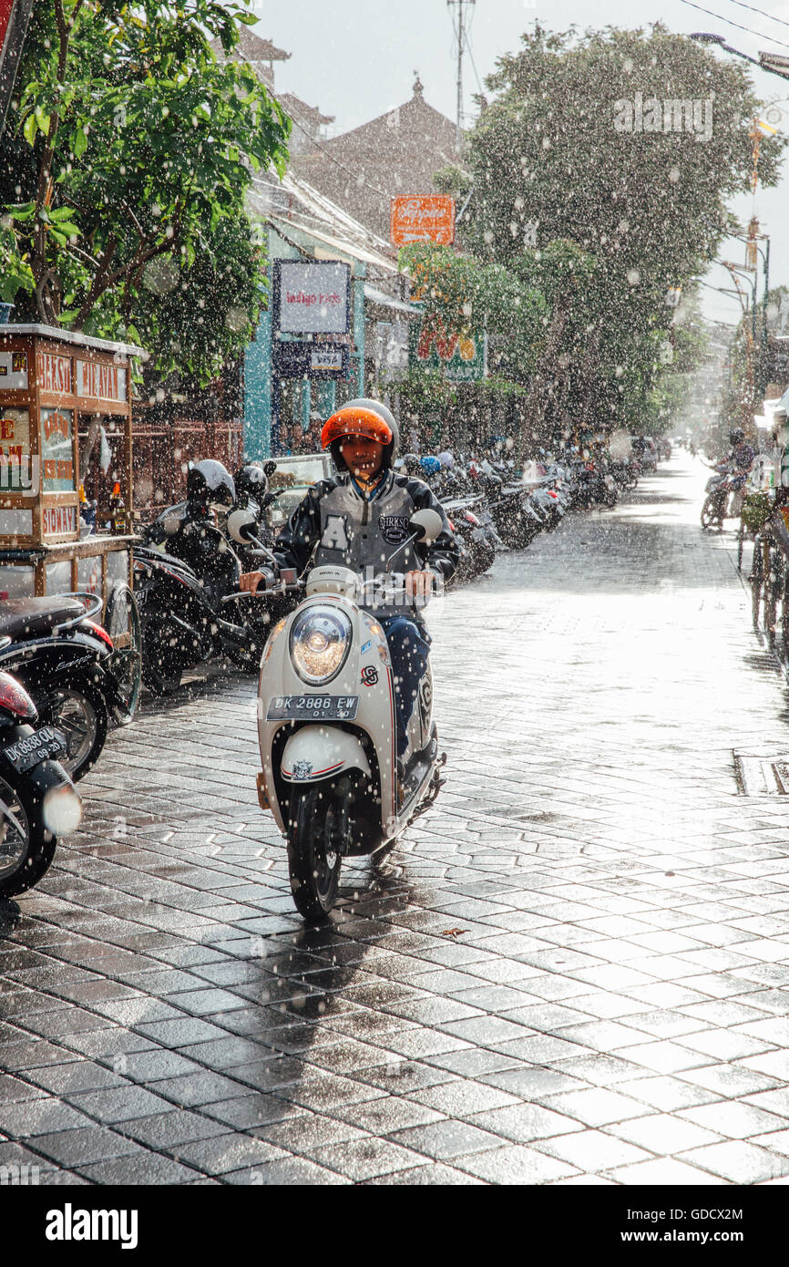 Indonesian man riding a motorbike under the rain on the street of Kuta, Bali, Indonesia. Stock Photo