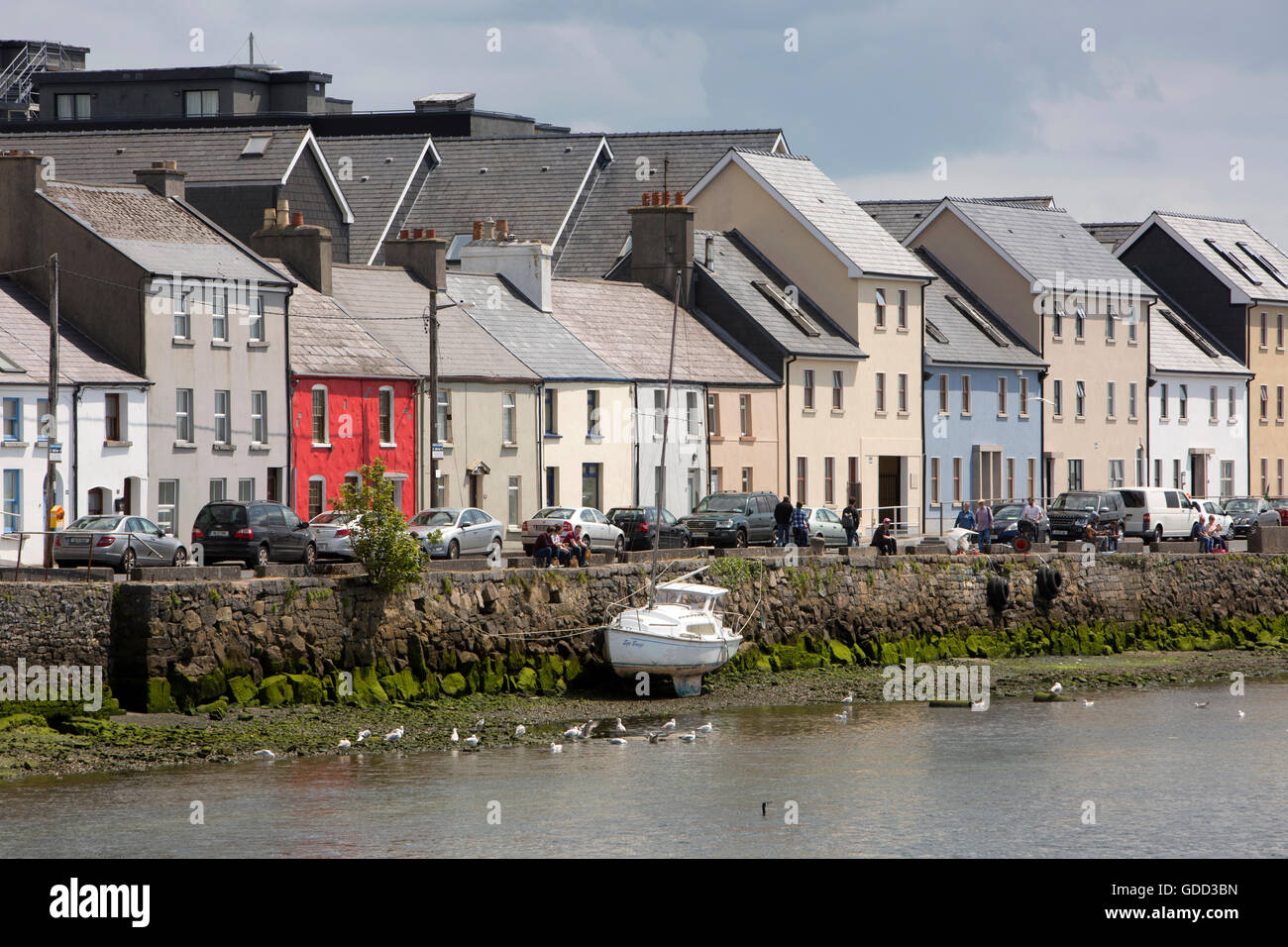 Ireland, Co Galway, Galway, boat beside colourfully painted Long Walk houses at low tide - Stock Image