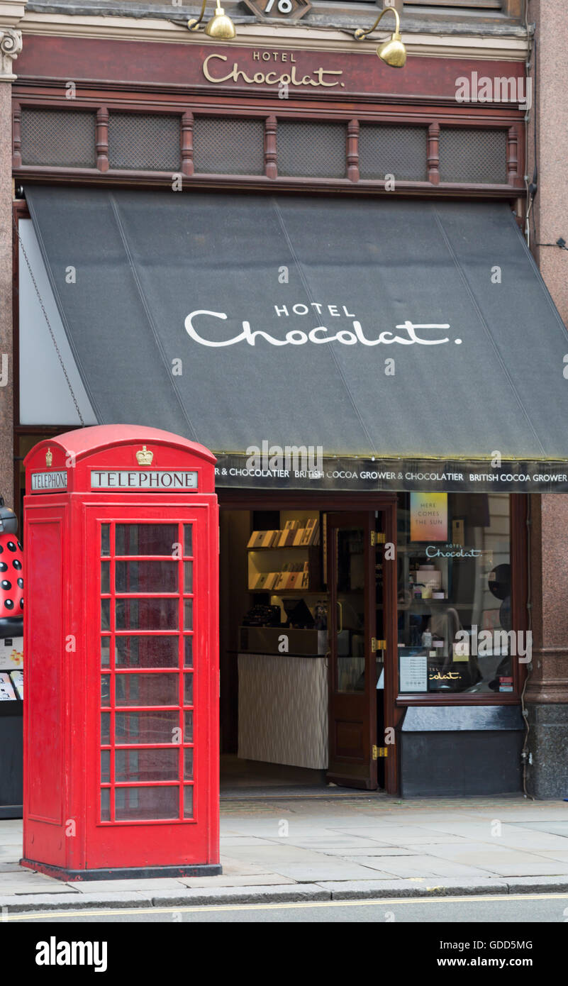 Red telephone box outside Hotel Chocolat, Strand, London in July - Stock Image