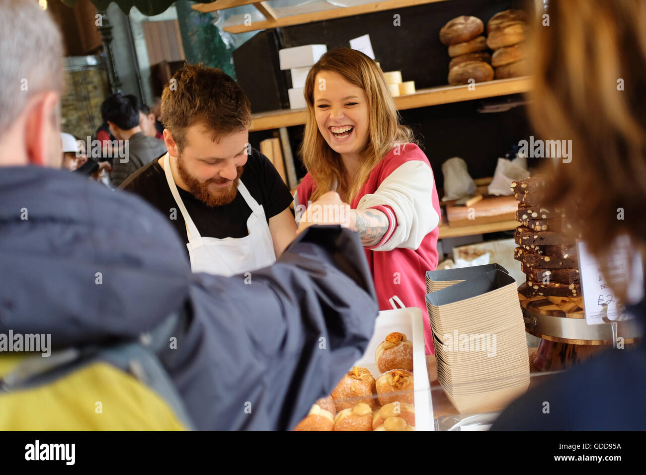 A stall owner handing change back to a shopper at Borough Market in London, England. - Stock Image