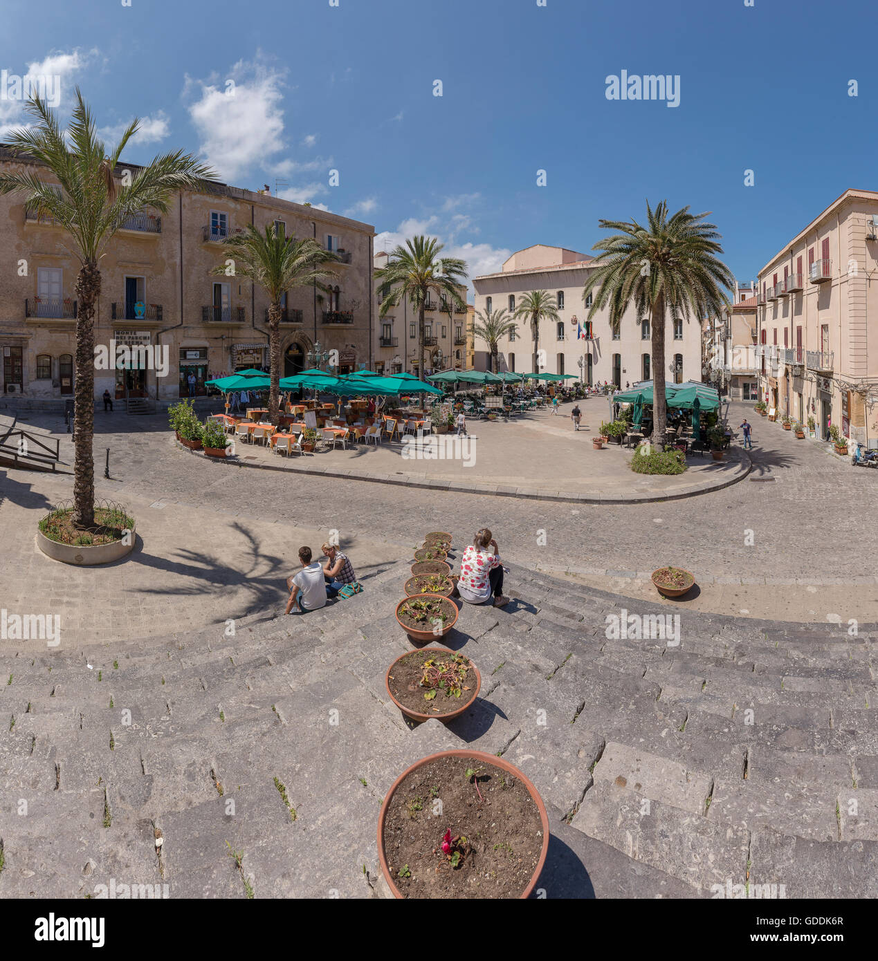 Square with outdoor cafes,sunshades and palm trees - Stock Image