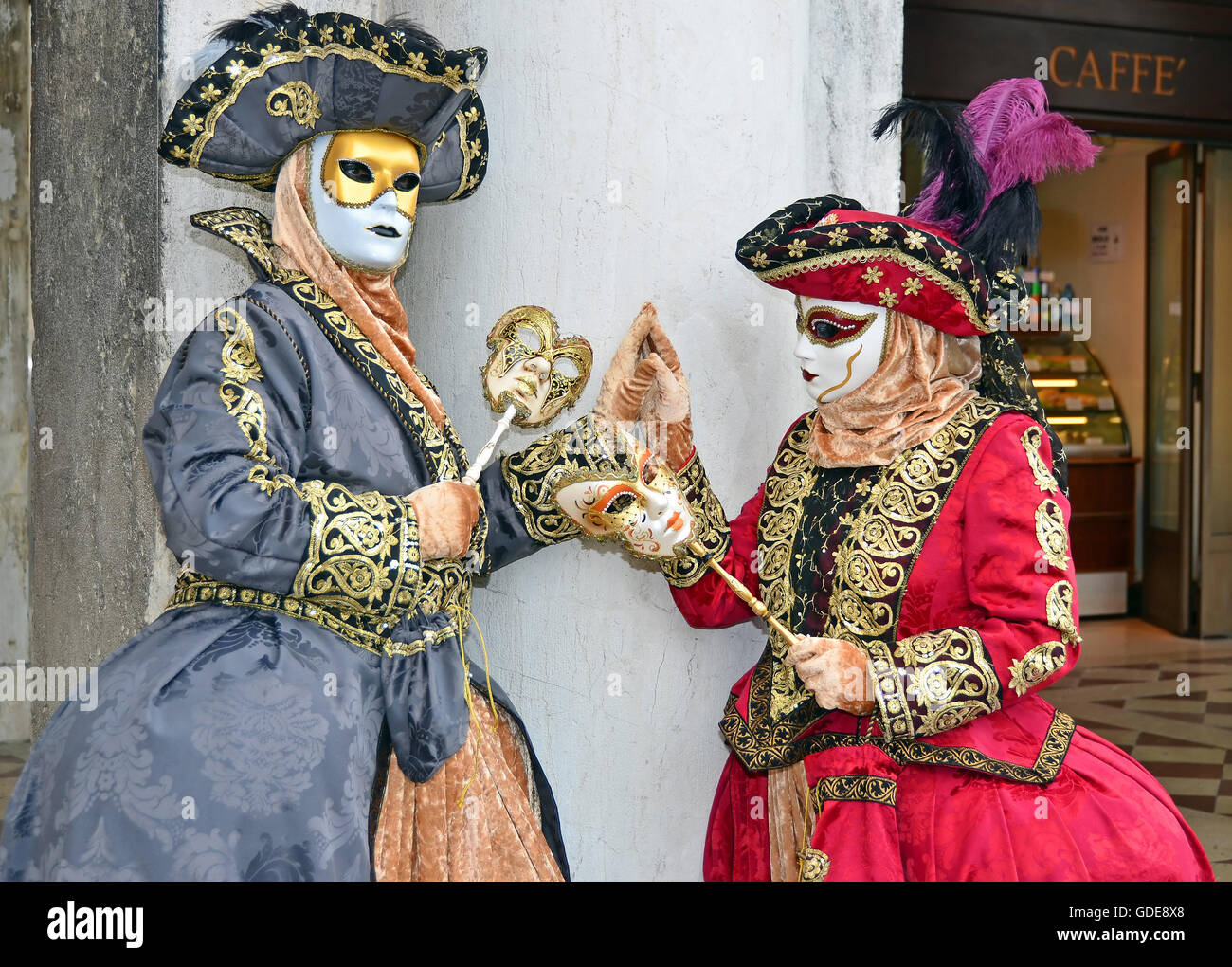 VENICE,ITALY - Two costumed ladies touching hands at the 2015 Venice Carnival: - Stock Image