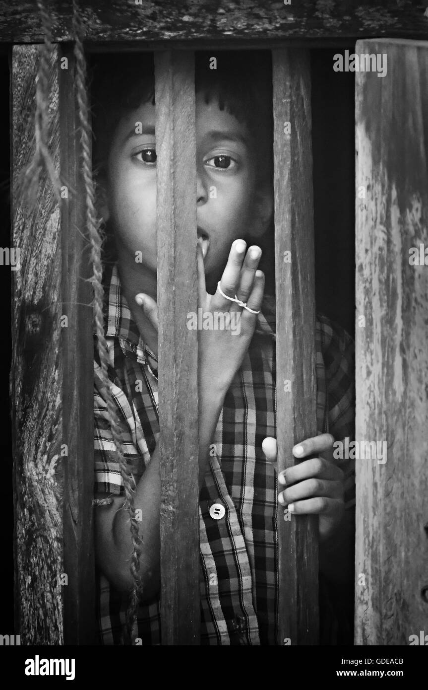 Unidentified Indian boy looks through a window at home in small fishing village. Black and white Stock Photo