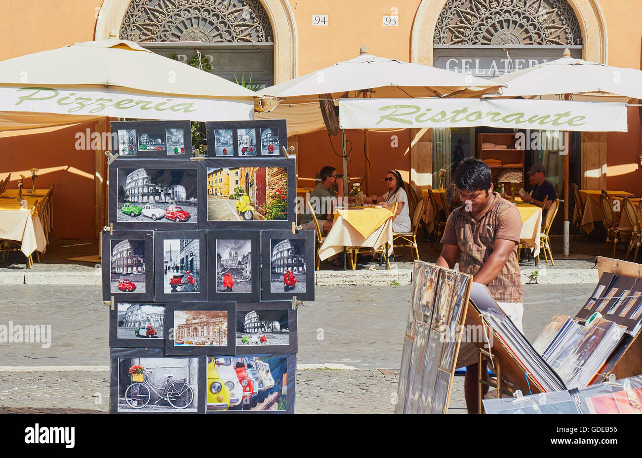Souvenir art for sale and alfresco restaurant terrace, Piazza Navona Rome Lazio Italy Europe - Stock Image