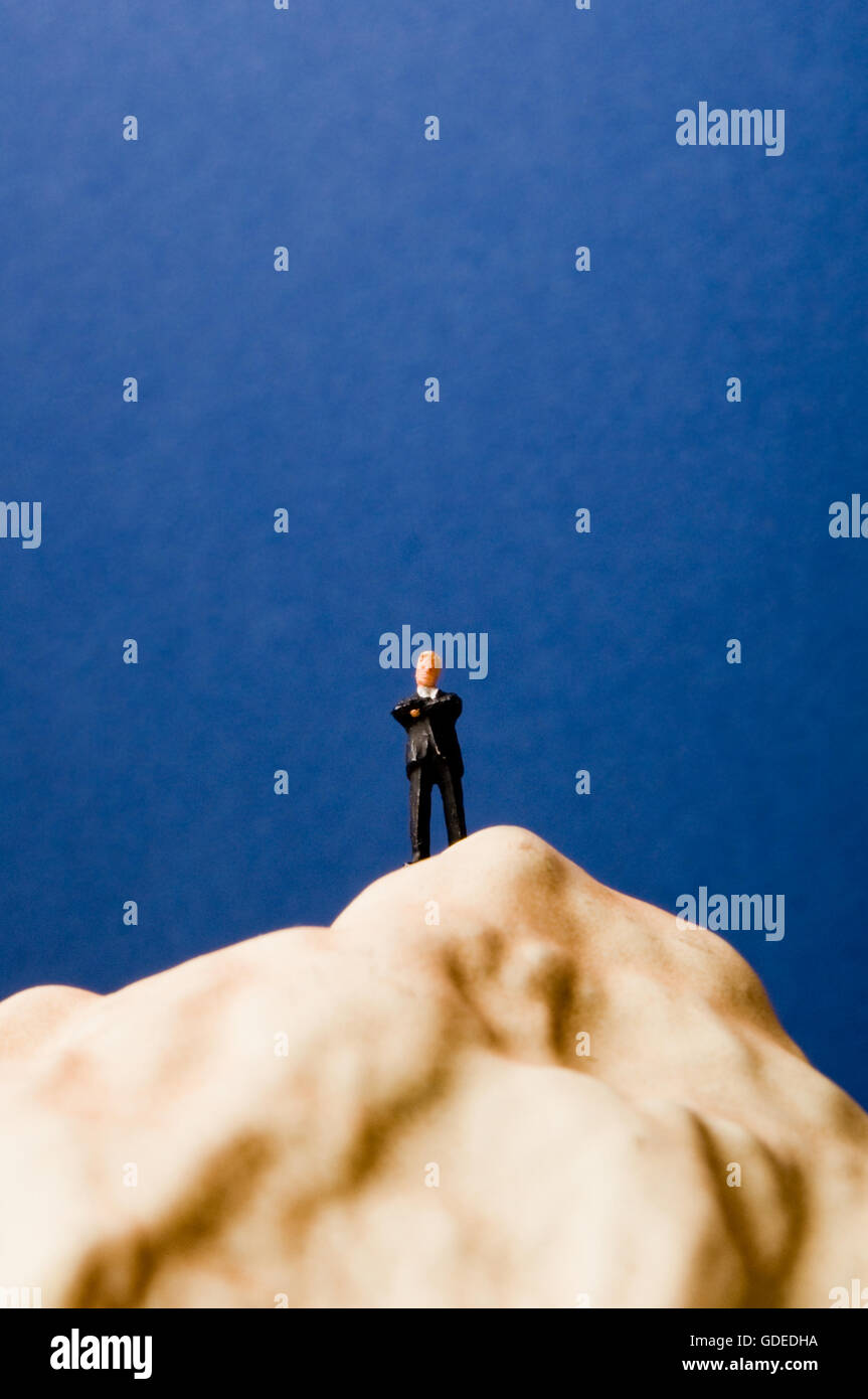 businessman miniature figurine on the top of a hill - Stock Image