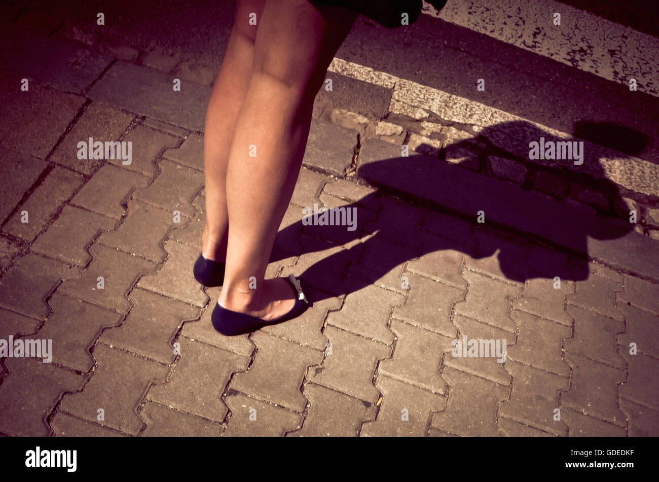 legs of an unknown woman standing in the street, her full figure shadow projected - Stock Image