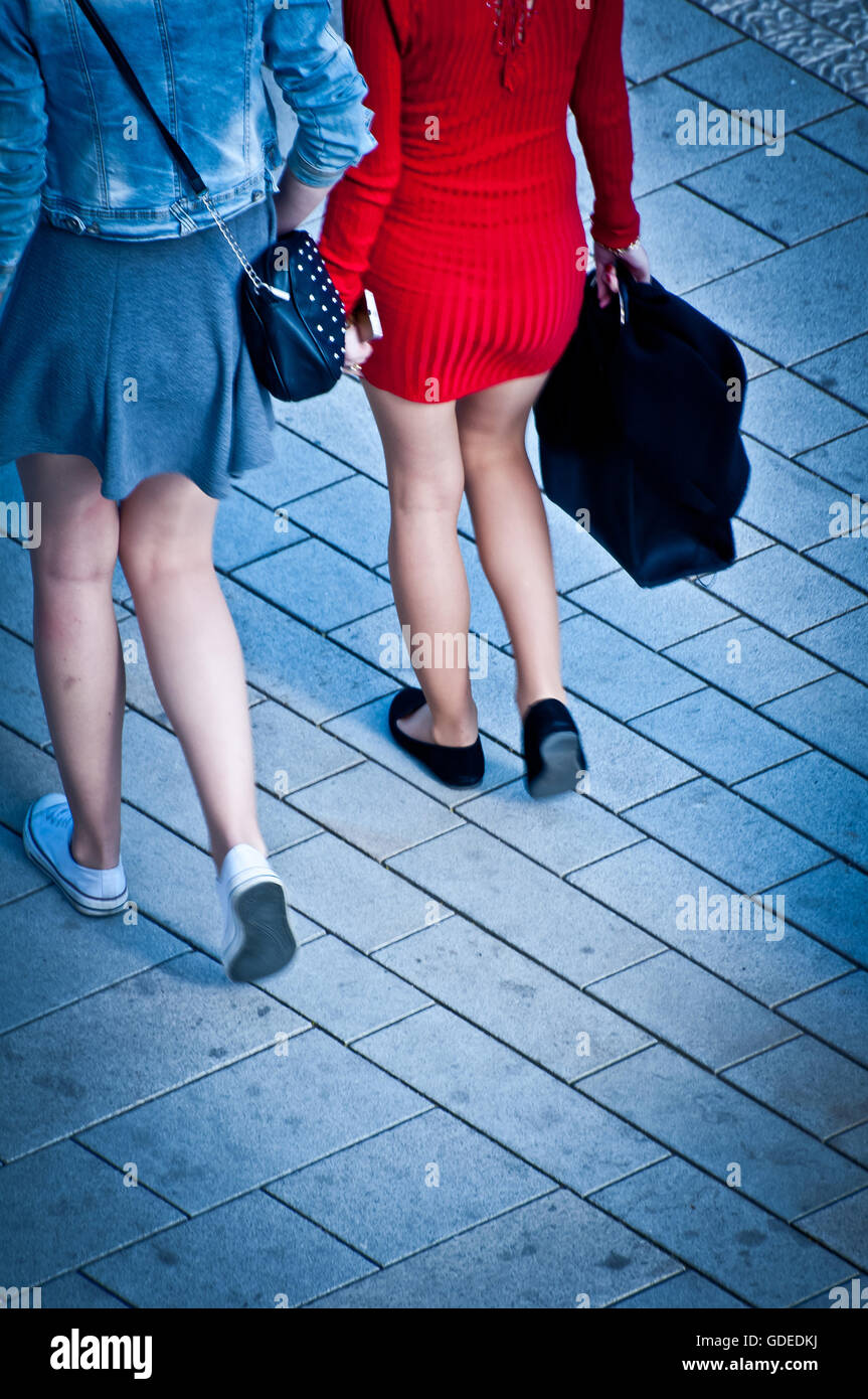 legs of a couple of girls walking in the street. view from above - Stock Image