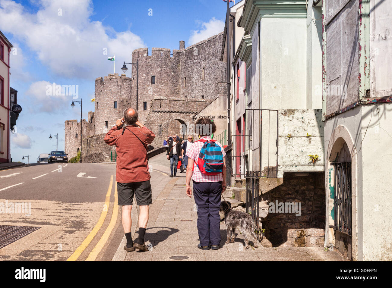 Visitor photographing the entrance to Pembroke Castle on Westgate Hill, Pembrokeshire, Wales,UK. - Stock Image