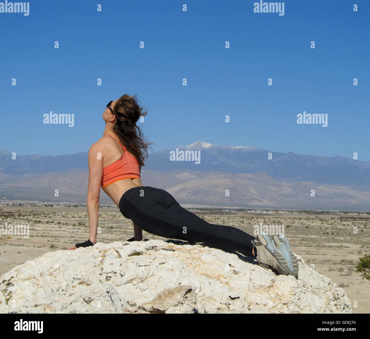 Woman doing an upward facing dog yoga pose on a rock in the desert, Nevada, America, USA - Stock Image