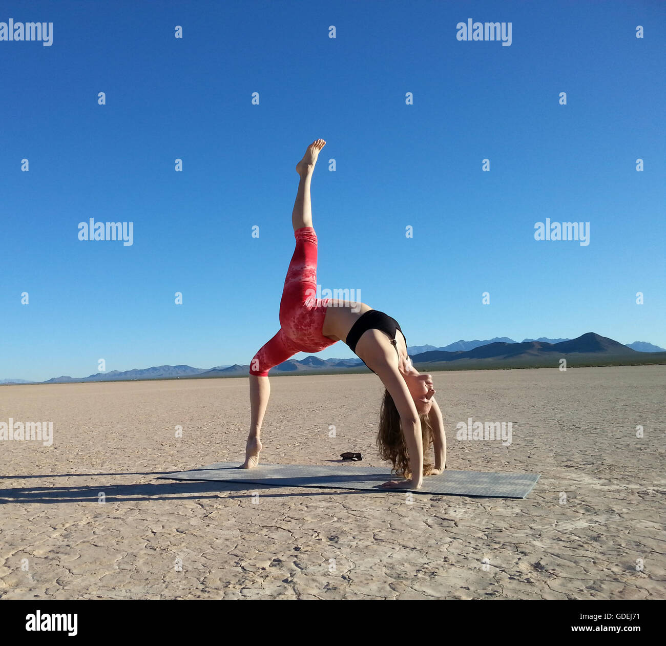 Woman doing a one legged wheel pose in a dry lake, Nevada, America, USA - Stock Image