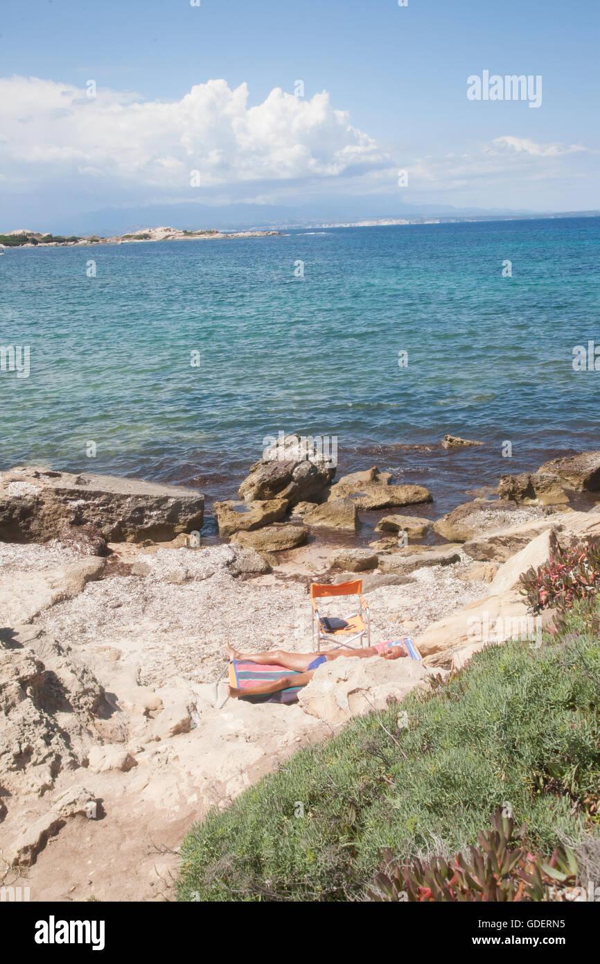 Italy, Sardegna, Capo Testa,  Rena di Ponente, sunbather by the rocks. - Stock Image