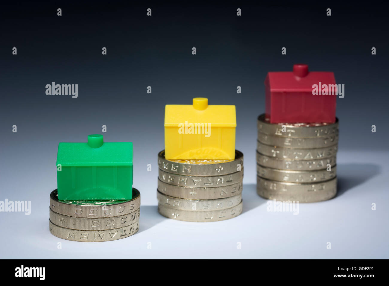 House / housing / property price inflation concept. Colorful toy houses placed on stacks of pound coins on neutral Stock Photo