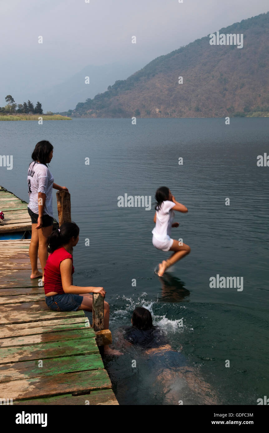 Children, swimming, jumping into Lago de Atitlan lake, San Lucas Toliman, Guatemala, Central America - Stock Image
