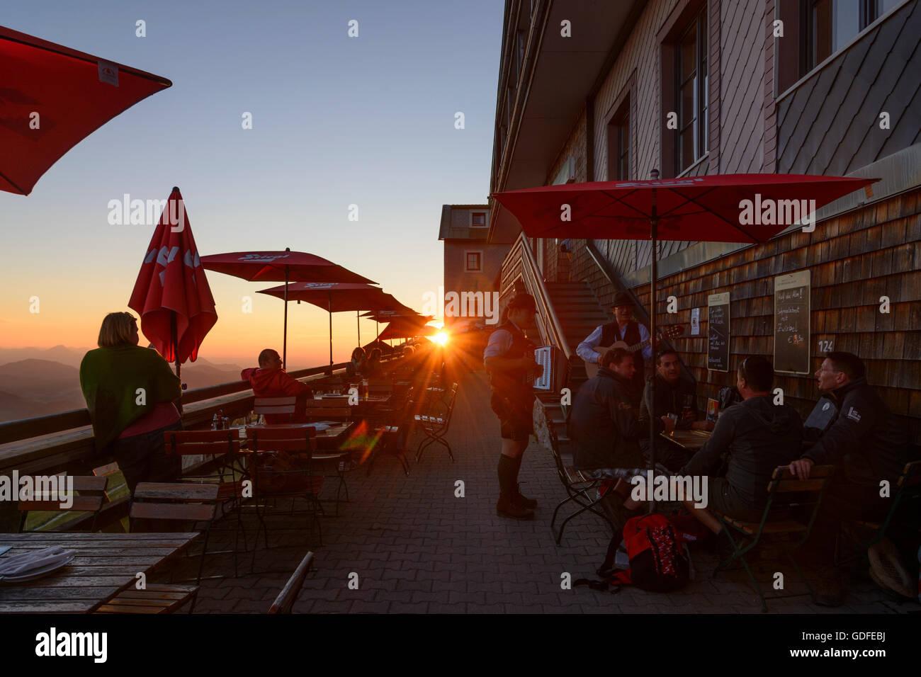 Sankt Gilgen: Accordion player and guests of Schafberghotel at sunset, Austria, Salzburg, Salzkammergut - Stock Image