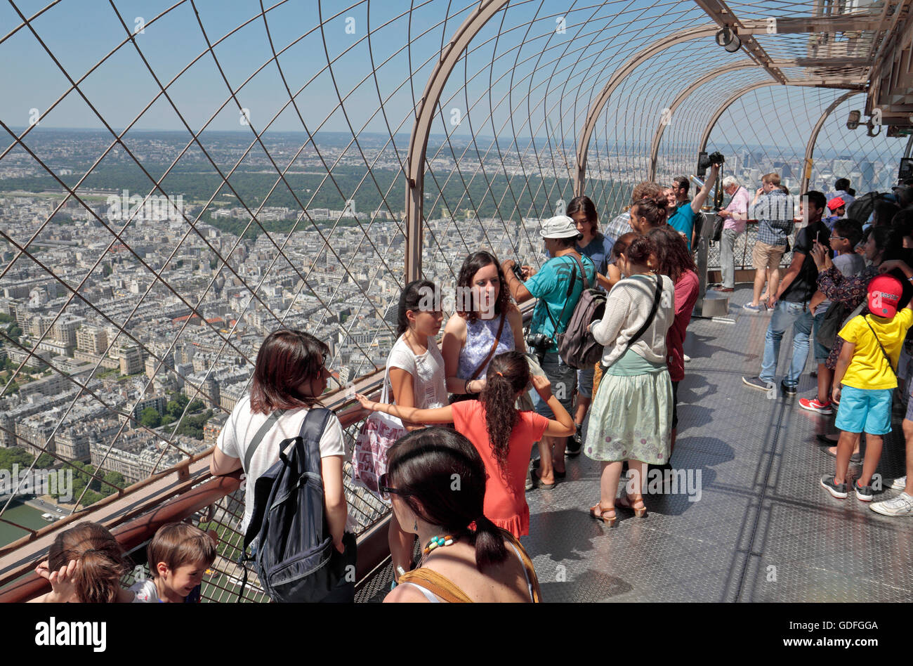 Tourists posing for photos on the upper level walkway of the Eiffel Tower in Paris, France. - Stock Image