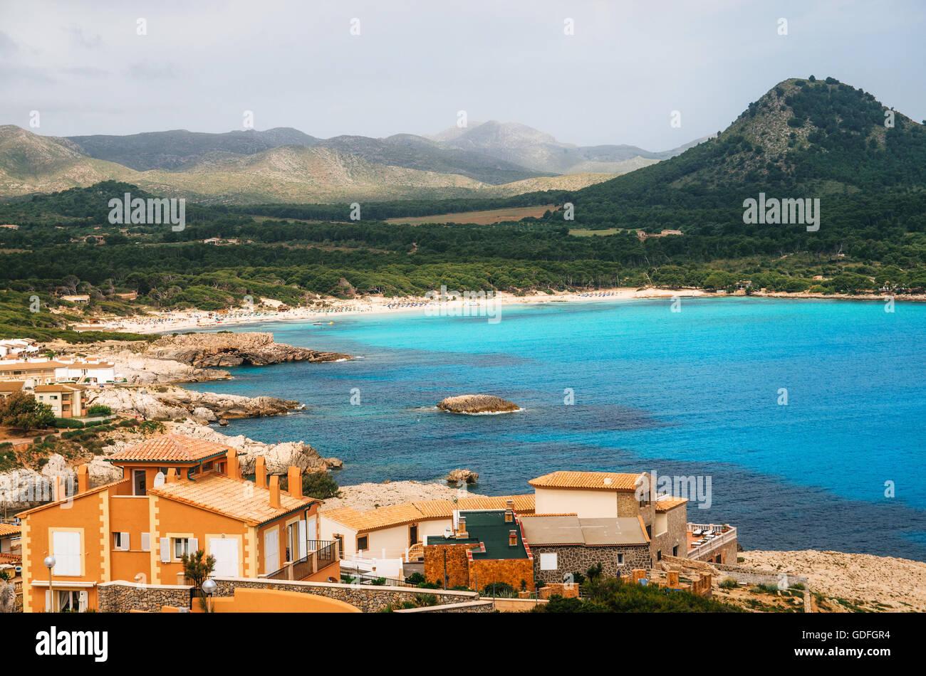 View of the Cala Agulla Beach in Mallorca island, Spain. Beautiful landscape with Es Pelats village, whitesand beach, - Stock Image