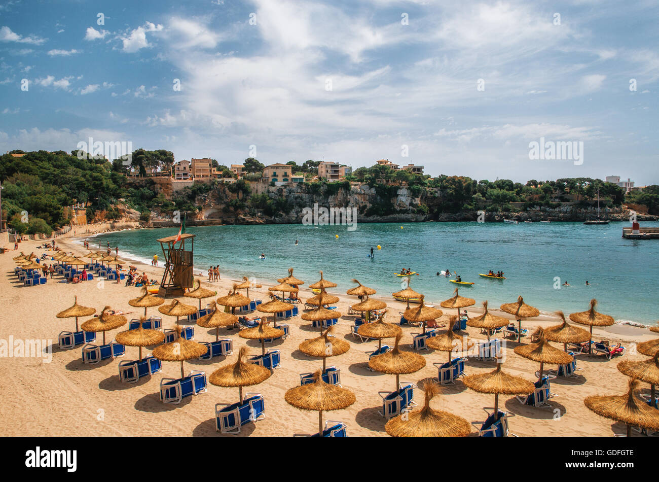 Straw umbrellas on the beach in Porto Cristo on Mallorca, Balearic Islands, Spain - Stock Image