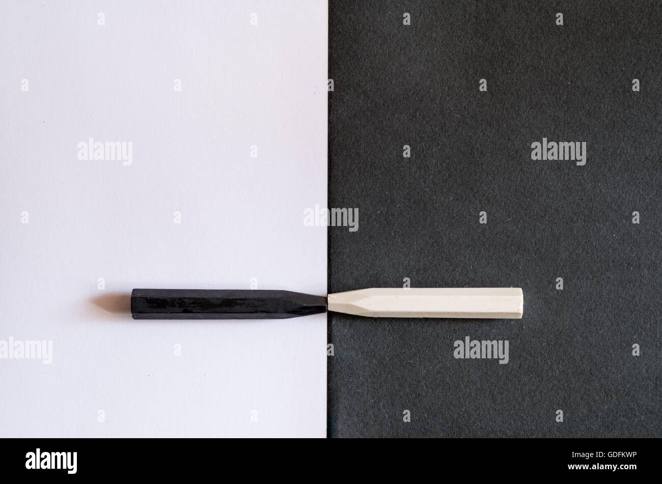 black and white crayons on alternate background of the same color, to symbolize the differences and similarities, - Stock Image