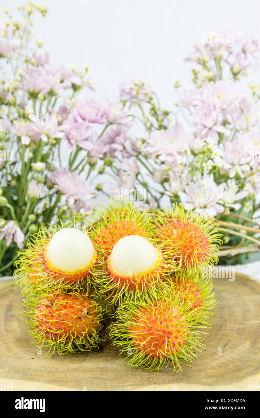 Fresh red rambutan sweet delicious fruit. Plum-sized tropical fruit with soft spines. - Stock Image