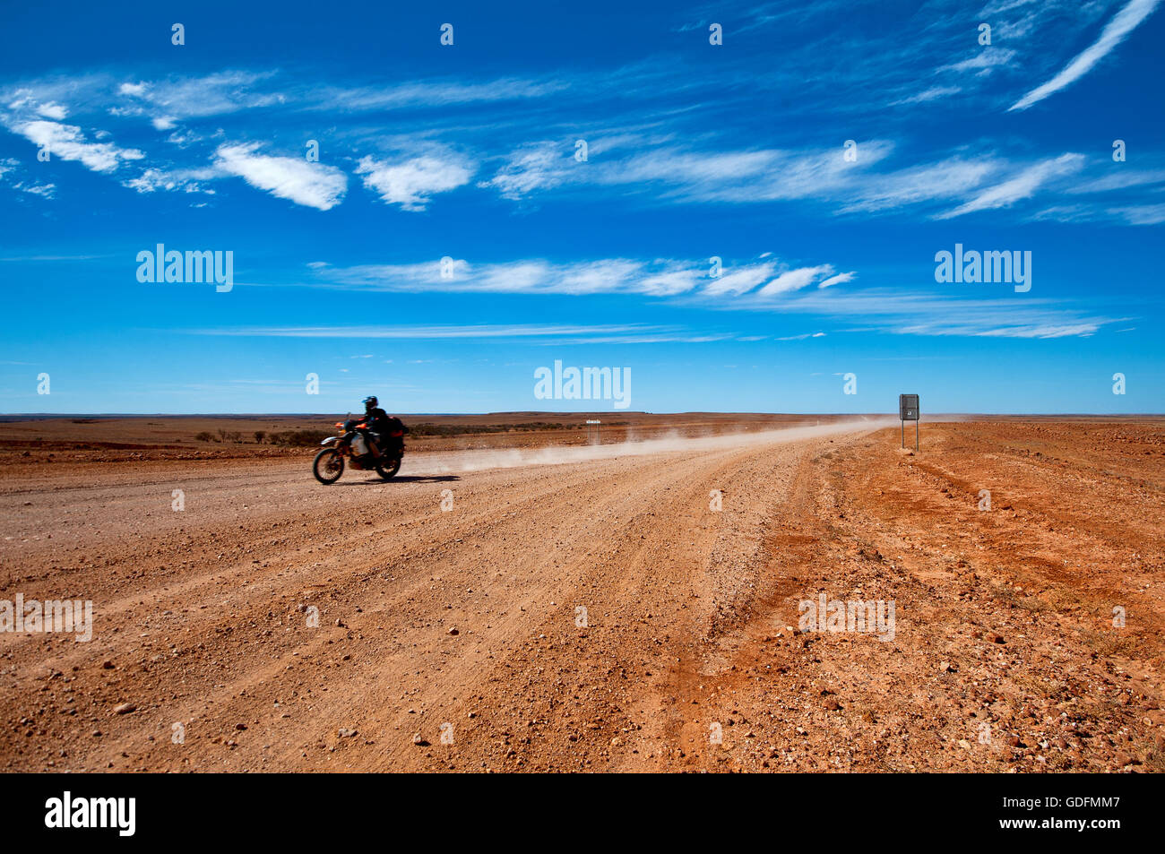 Biker on a desert track in Queensland outback. - Stock Image
