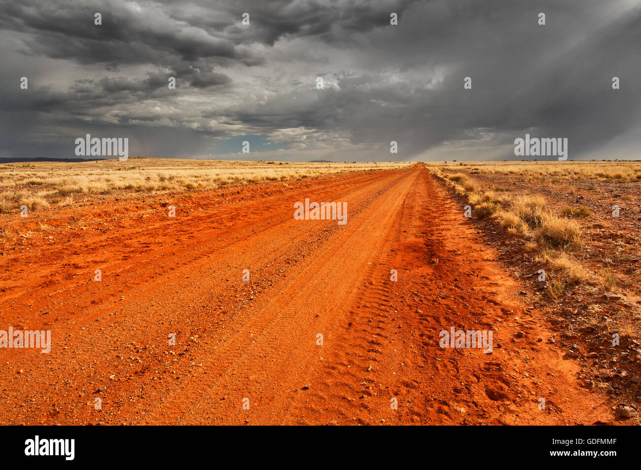 Dark clouds approaching on a desert track. - Stock Image