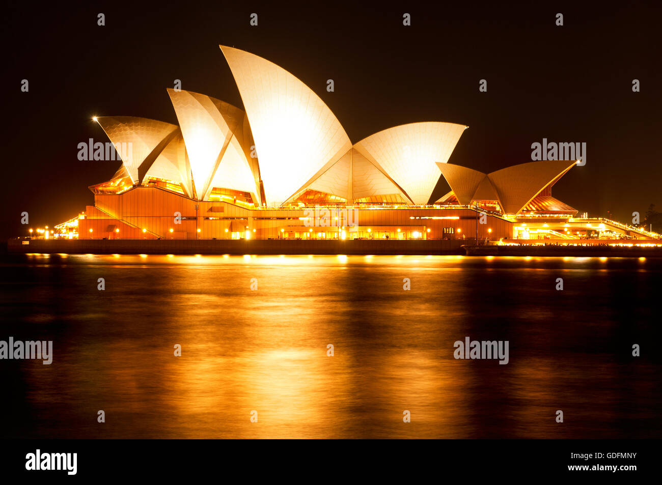 Illuminated Sydney Opera House reflects in the water of the harbour. - Stock Image