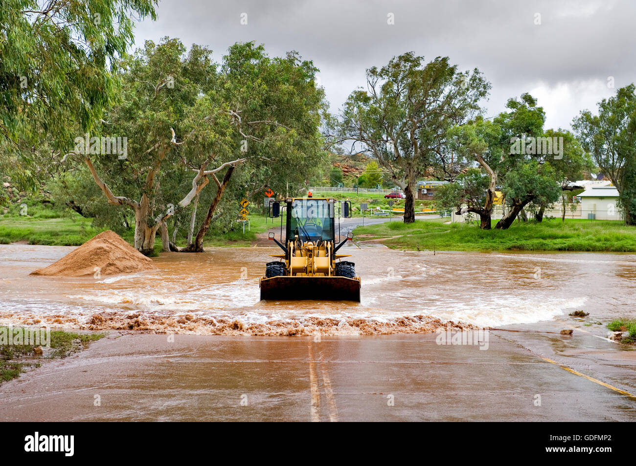 Wheel Loader cleaning a road in Alice Springs after a Todd River flood. - Stock Image