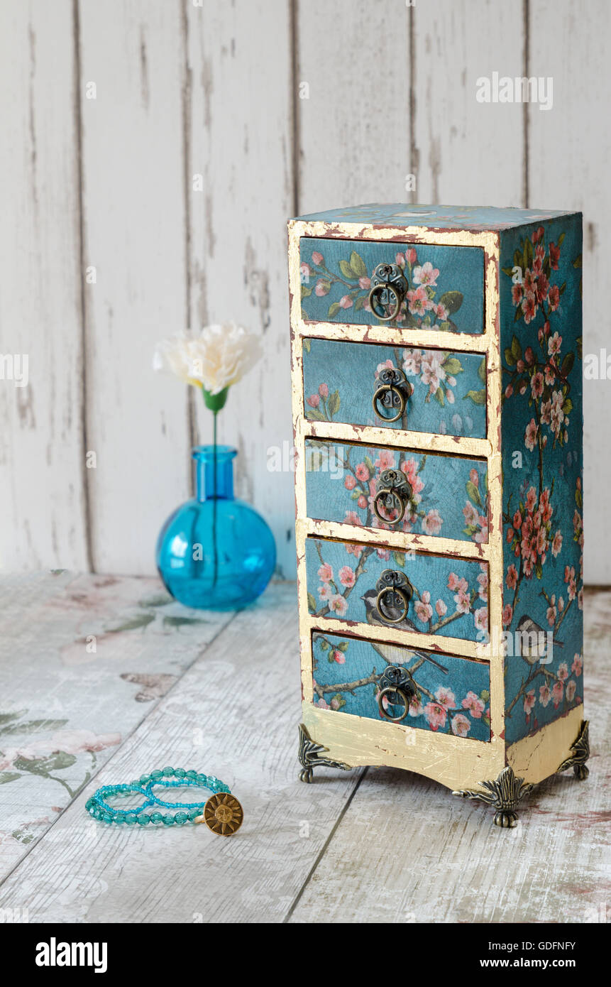 Handmade gilded mini chest of drawers in a vintage floral style - Stock Image