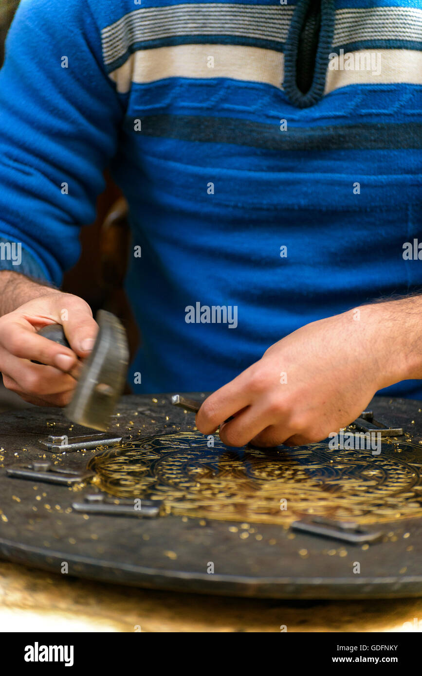 Two Hands of Craftsman Engraving Decorative Brass Masterpiece - Stock Image