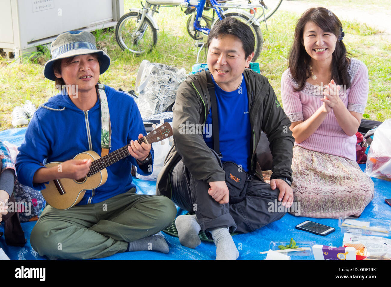 Three Japanese people at a picnic, one of which is playing a ukulele. - Stock Image