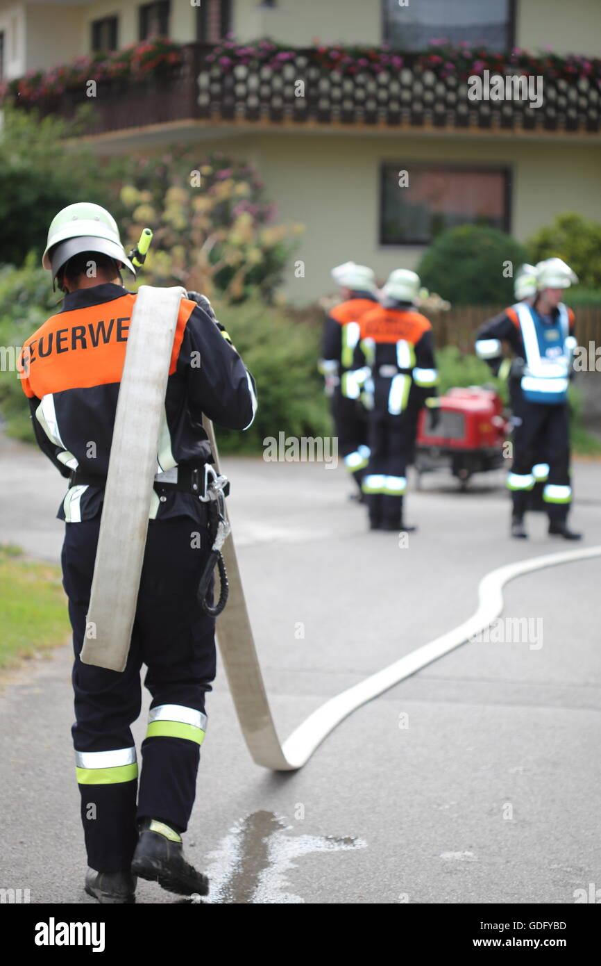 A Fireman with hose over shoulder shoulders - Stock Image