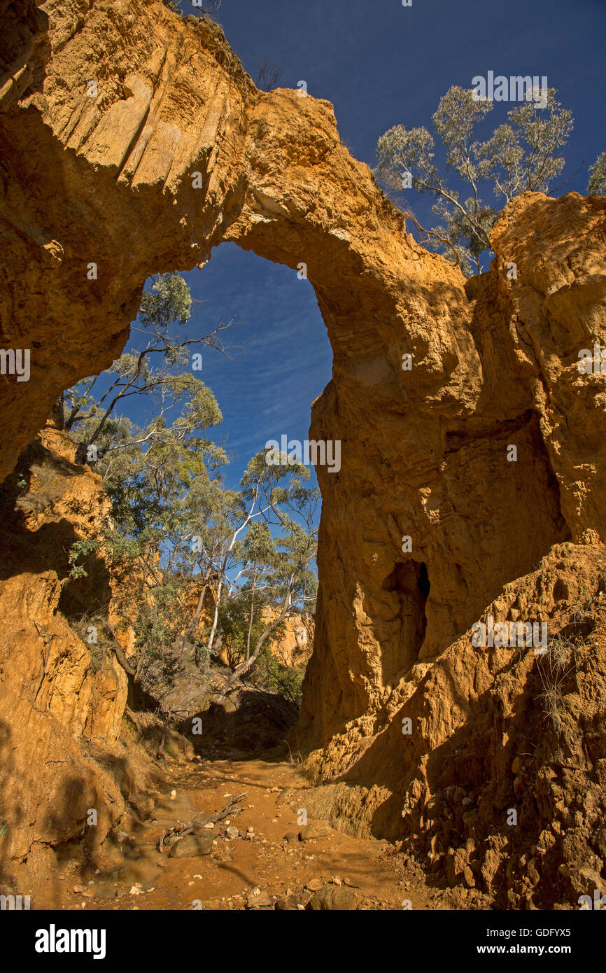 Picturesque high natural red stone arch over narrow eroded gully with deep blue sky visible through & above - Stock Image