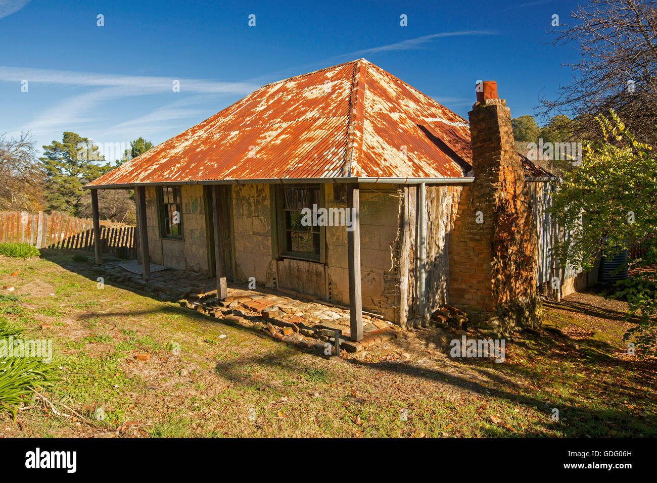 Historic building, old  miner's cottage with rusty roof, red brick chimney, flaking paint, against blue sky at Hill Stock Photo