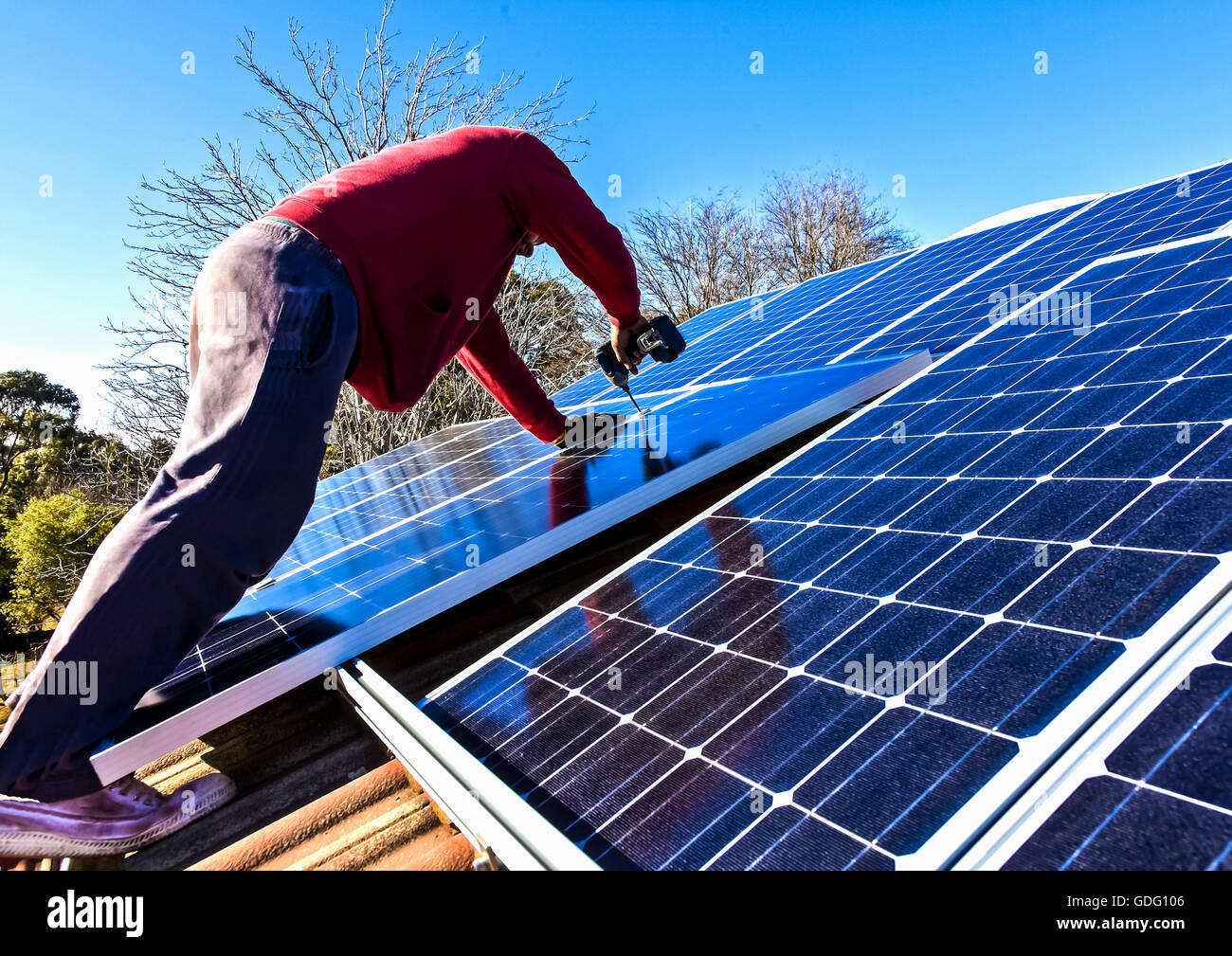 Fitting solar panels to roof of house - Stock Image