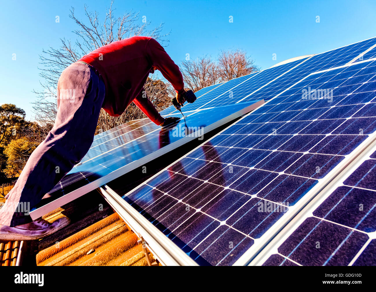 Workman installing solar panels on house roof - Stock Image